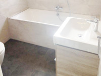 A stunning bathroom with a walk in shower, bath and wash hand basin fitted by our bathroom fitters.